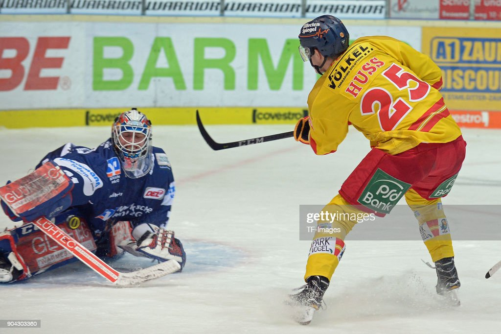 Johannes Huss of Duesseldorf and Goalkeeper Sebastian Dahm of Iserlohn in action during the DEL match between Iserlohn Roosters and Duesseldorfer EG at Eissporthalle Iserlohn on January 12, 2018 in Iserlohn, Germany.