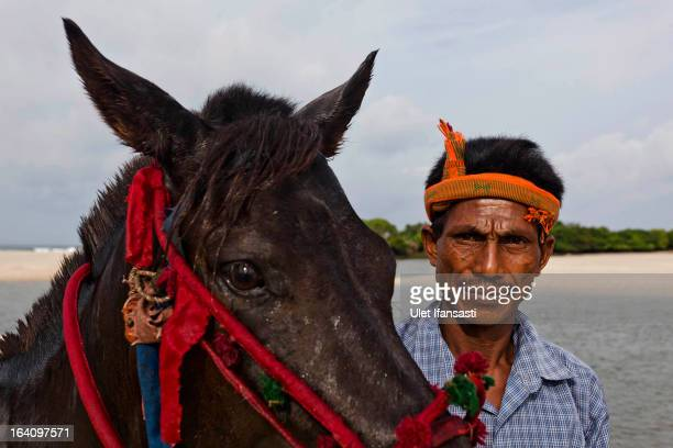 Johannes Ndara Kepala stands with his freshly bathed and decorated horse for The Pasola on March 4 2013 in Sumba Island East Nusa Tenggara Indonesia...