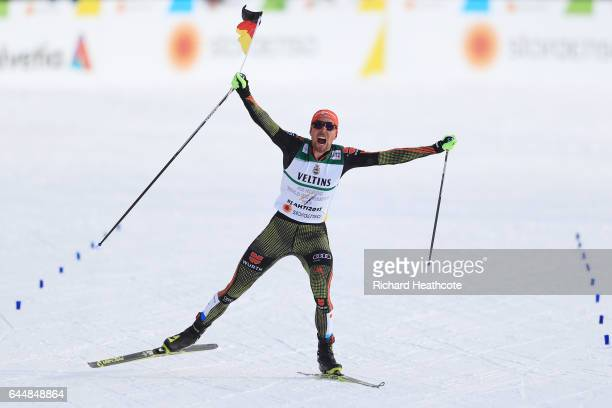 Johannes Rydzek of Germany celebrates winning the gold as he approaches the finish line in the Men's Nordic Combined 10KM Cross Country during the...