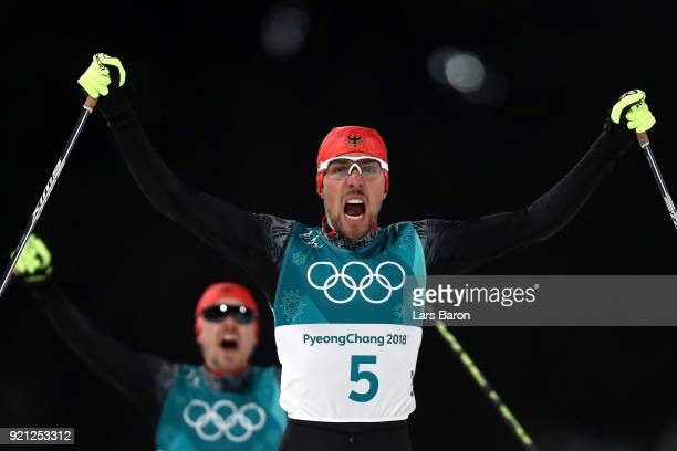 Johannes Rydzek of Germany celebrates winning the gold medal followed by silver medallist Fabian Riessle of Germany during the Nordic Combined...
