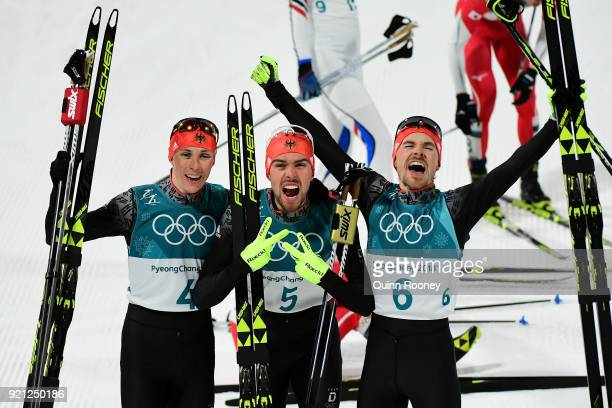 Johannes Rydzek of Germany celebrates winning the gold medal with silver medallist Fabian Riessle of Germany and bronze medallist Eric Frenzel of...