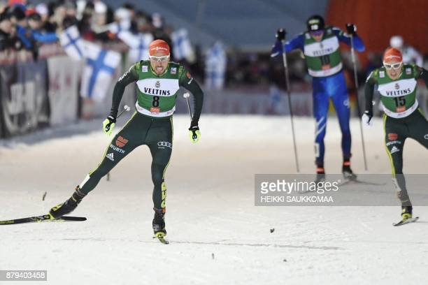Johannes Rydzek of Germany crosses the finish line to win the Nordic Combined Men's Individual Gundersen 10 km competition in front of his compatriot...