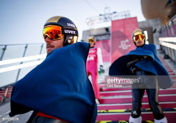 Johannes Rydzek of Germany tries to keep warm at the Normal Hill next to his team mates Eric Frenzel and Fabian Riessle during the Nordic Combined...