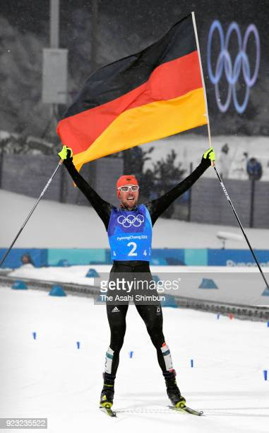 Johannes Rydzek of Germany wave the national flag as he celebrates winning the gold medal in the Nordic Combined Team Gundersen Large Hill/4x5km...