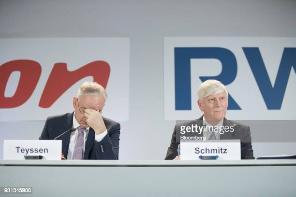 Johannes Teyssen chief executive officer of EON SE left reacts as he sits beside Rolf Schmitz chief executive officer of RWE AG during a news...