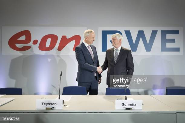 Johannes Teyssen chief executive officer of EON SE left shakes hands with Rolf Schmitz chief executive officer of RWE AG during a news conference in...