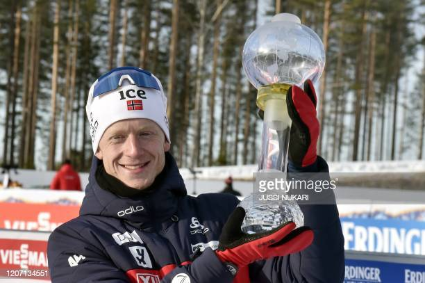 Johannes Thingnes Boe of Norway celebrates with the trophy for the overall victory in the season's World Cup after the men's 125 km Pursuit...