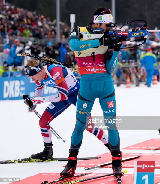 Johannes Thingnes Boe of Norway  leaves the shooting stand ahead of Martin Fourcade of France during the men's mass start event of the Biathlon World...