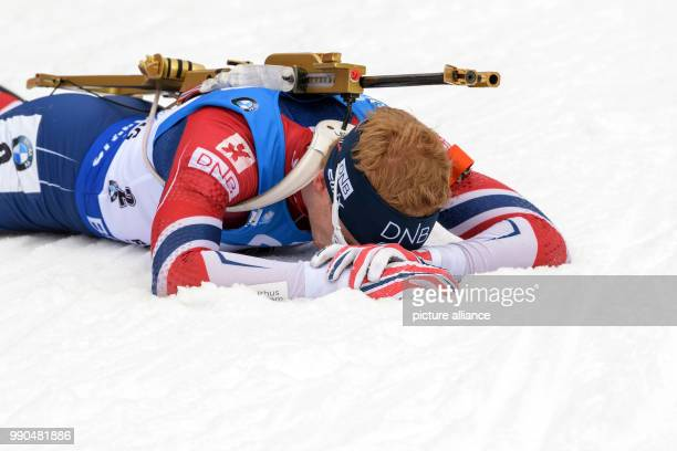 Johannes Thingnes Boe of Norway lies on the ground at the finish line during the men's mass start event of the Biathlon World Cup at the Chiemgau...