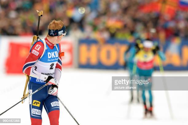 Johannes Thingnes Boe of Norway  looks back at Martin Fourcade of France at the finish line during the men's mass start event of the Biathlon World...