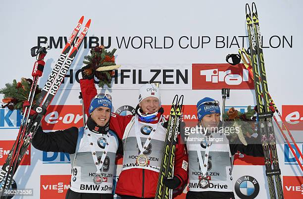 Johannes Thingnes Boe of Norway poses on the podium with second placed Simon Schempp of Germany and third placed Andreas Birnbacher of Germany the...