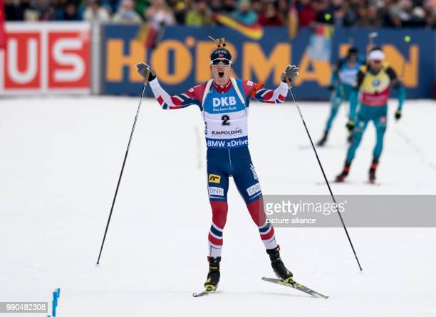 Johannes Thingnes Boe of Norway reaches the finish line ahead of Martin Fourcade of France during the men's mass start event of the Biathlon World...