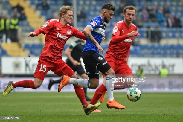 Johannes van den Bergh and Dominic Peitz of Kiel tackle Keanu Staude of Bielefeld during the Second Bundesliga match between DSC Arminia Bielefeld...