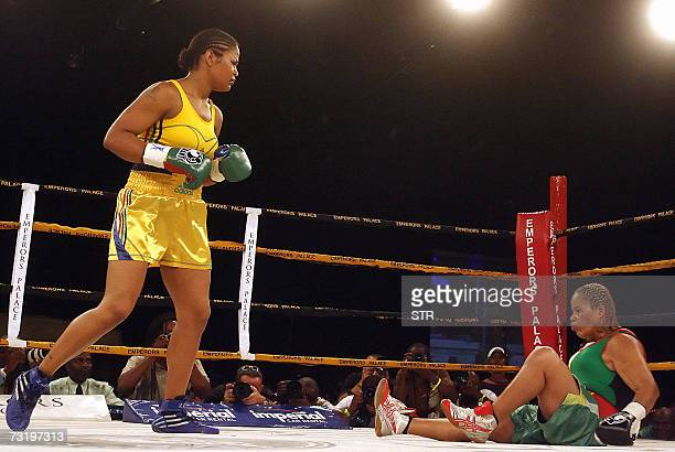 Laila Ali boxing champion and daughter of boxing legend Muhammad Ali' looks at her opponent Guyanan boxer Gwendolyn O' Neill after flooring her...