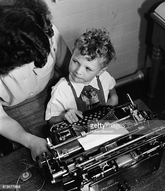 John, a spastic child learns to type his name on a typewriter.