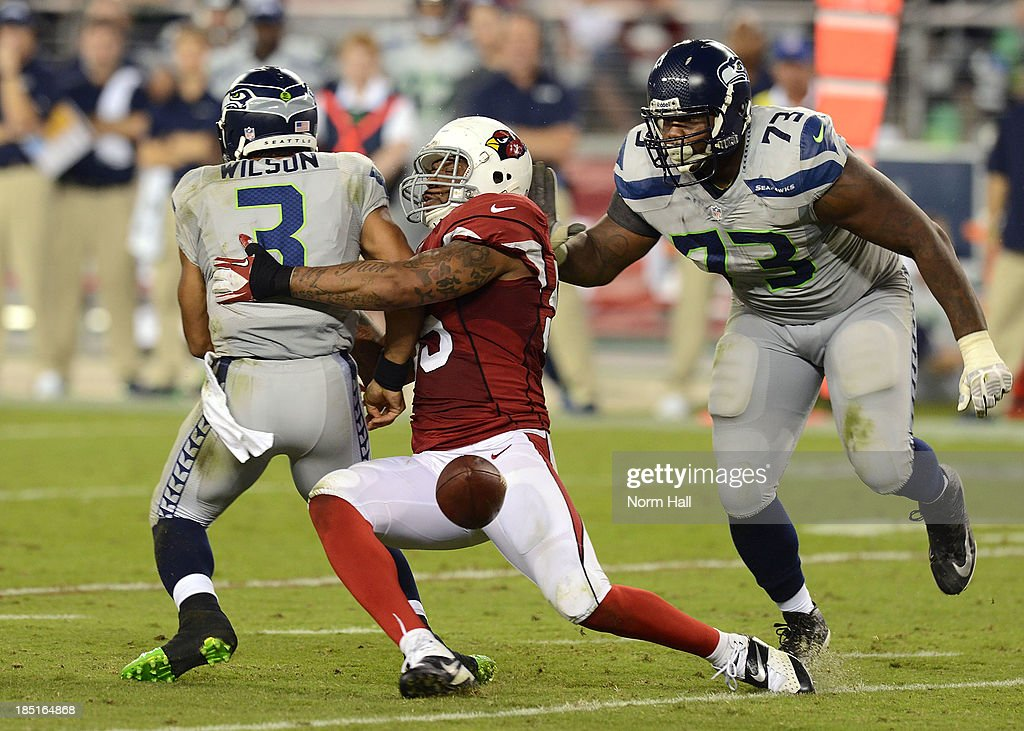 John Abraham #55 of the Arizona Cardinals knocks the ball away Russell Wilson #3 of the Seattle Seahawks at University of Phoenix Stadium on October 17, 2013 in Glendale, Arizona.