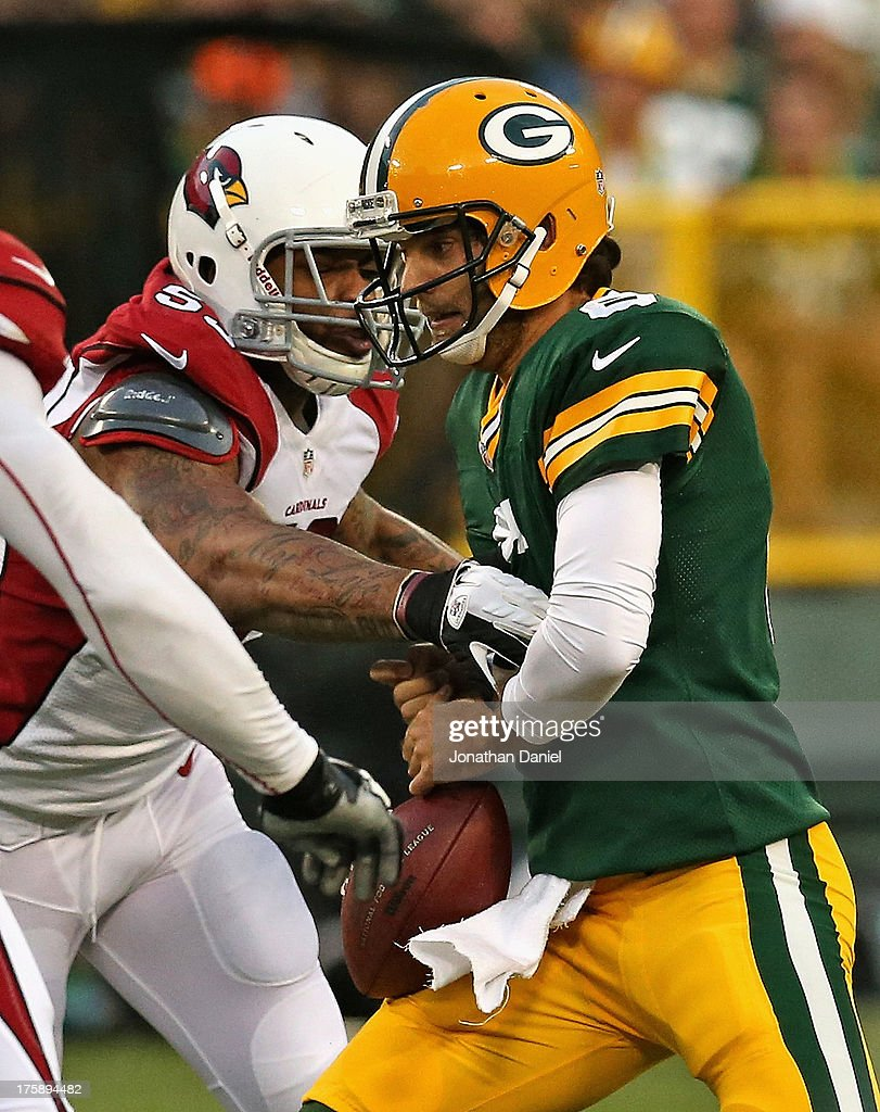 John Abraham #53 of the Arizona Cardinals strips the ball from Graham Harrell #6 at Lambeau Field on August 9, 2013 in Green Bay, Wisconsin.
