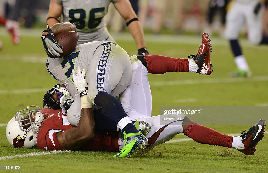 John Abraham #55 of the Arizona Cardinals tackles Marshawn Lynch #24 of the Seattle Seahawks at University of Phoenix Stadium on October 17, 2013 in Glendale, Arizona.
