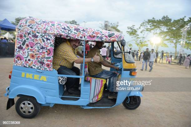 John Achillea managing director of Ikea India rides in an auto rickshaw painted in Ikea colours at a promotional event for the new Ikea furniture...