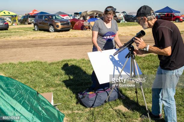 John Adlington and Tricia Dacie successfully setup a telescope to project an image of the Sun on a white matte board. They are some of the total...