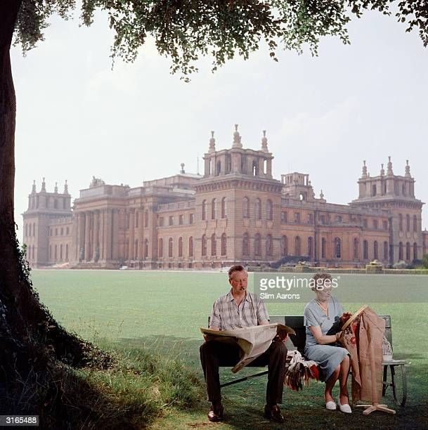 John Albert Edward Spencer Churchill, the 10th Duke of Marlborough and his wife Mary relax on a bench in the grounds of Blenheim Palace, the family...