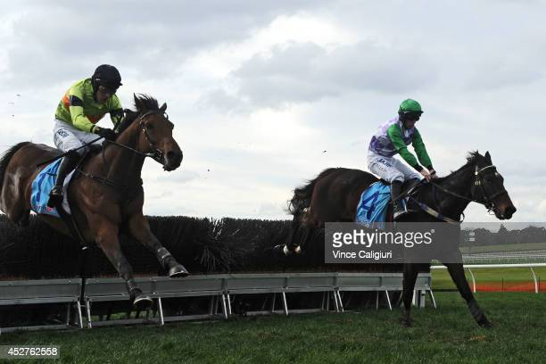 John Allen riding Wells jumps the last steeple before defeating Steven Pateman riding Bashboy in Race 4 the Grand National Steeplechase during the...