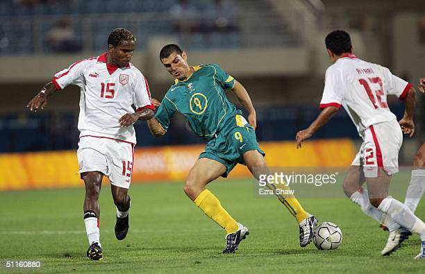 John Aloisi of Australia dribbles between Clayton and Anis Ayari of Tunisia during the men's football preliminary match on August 11 2004 during the...