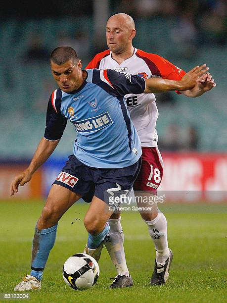 John Aloisi of Sydney FC contests the ball with Daniel Tiatto of Queensland Roar during the round seven A-League match between Sydney FC and...