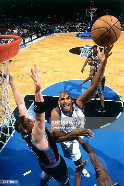 John Amaechi of the Orlando Magic shoots against Bryant Reeves of the Vancouver Grizzlies during a game played in 2000 at the TD Waterhouse Center in...