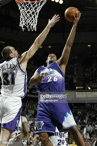 John Amaechi of the Utah Jazz shoots past Scot Pollard of the Sacramento Kings in Game five of the Western Conference Quarterfinals during the 2003...