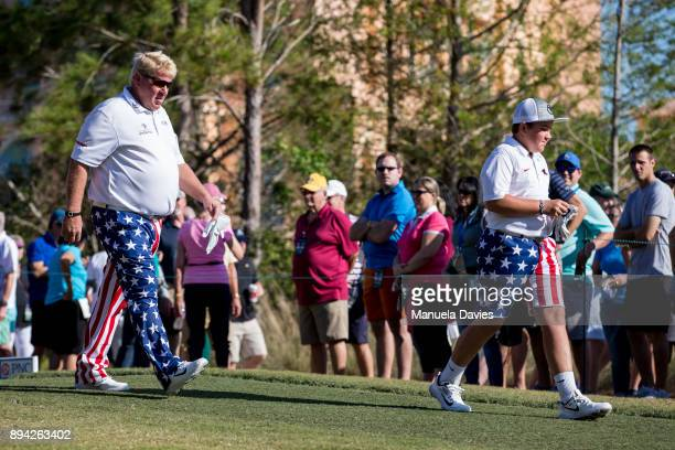 John and Little John Daly walk off the first tee during the final round of the PNC Father/Son Challenge at The RitzCarlton Golf Club on December 17...
