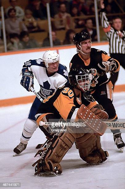 John Anderson of the Toronto Maple Leafs battles for position against Rod Buskas behind goalie Roberto Romano of the Pittsburg Penguins during game...