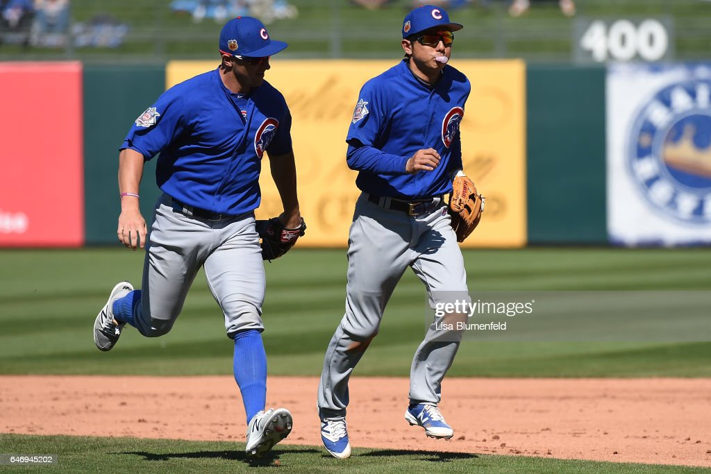 John Andreoli #72 and Munenori Kawasaki #66 of the Chicago Cubs run off the field in the fourth inning against the Kansas City Royals at Surprise Stadium on March 1, 2017 in Surprise, Arizona.