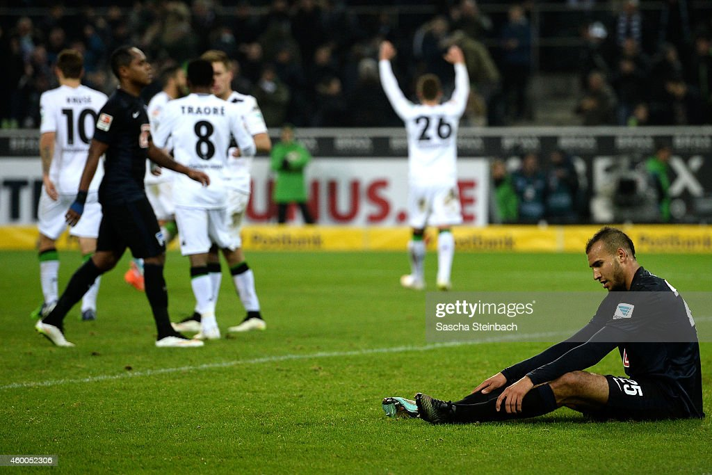 John Anthony Brooks (R) of Berlin reacts as Thorgan Hazard (C) of Moenchengladbach celebrates his team's third goal during the Bundesliga match between Borussia Moenchengladbach and Hertha BSC Berlin at Borussia Park Stadium on December 6, 2014 in Moenchengladbach, Germany.
