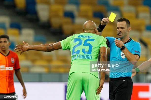 John Anthony Brooks of VfL Wolfsburg and referee Ivan Kruzliak Yellow Card during the UEFA Europa League round of 16 second leg match between...