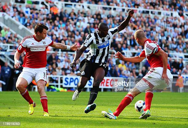 John Arne Riise and Brede Hangeland of Fulham challenge Shola Ameobi of Newcastle United during the Barclays Premier League match between Newcastle...