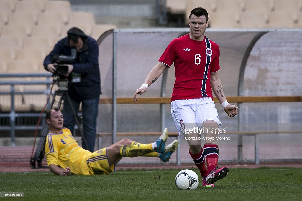 John Arne Riise (R) of Norway controls the ball as Oleh Husyev (L) of Ukraine falls down on the ground during the international friendly football match between Norway and Ukraine at Estadio Olimpico de Sevilla on February 6, 2013 in Seville, Spain.