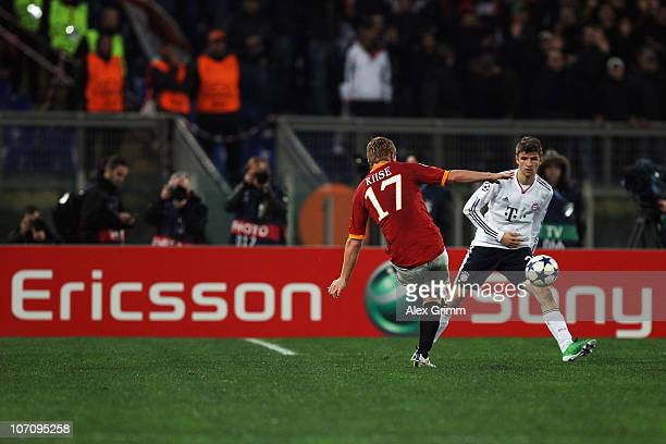 John Arne Riise of Roma is challenged by Thomas Mueller of Muenchen in front of the Sony Ericsson advertisement board during the UEFA Champions...