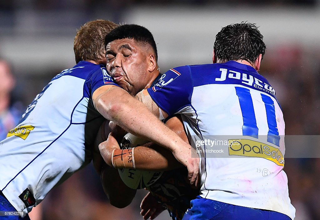John Asiata of the Cowboys is tackled by Joshua Jackson and Aiden Tolman of the Bulldogs during the round 20 NRL match between the North Queensland Cowboys and the Canterbury Bulldogs at 1300SMILES Stadium on July 21, 2016 in Townsville, Australia.