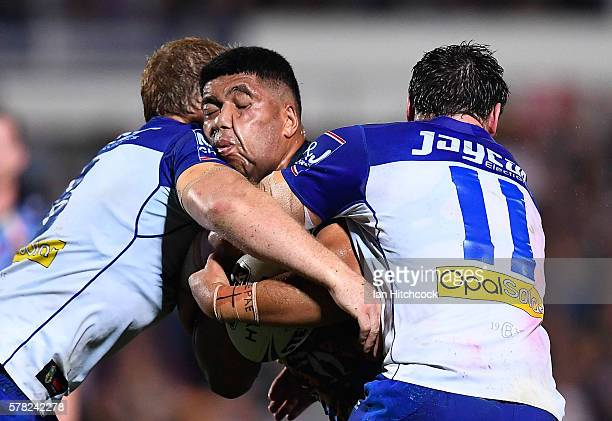 John Asiata of the Cowboys is tackled by Joshua Jackson and Aiden Tolman of the Bulldogs during the round 20 NRL match between the North Queensland...