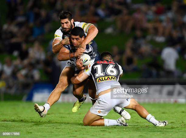 John Asiata of the Cowboys is tackled by Moses Leota and James Tamou of the Panthers during the round four NRL match between the North Queensland...