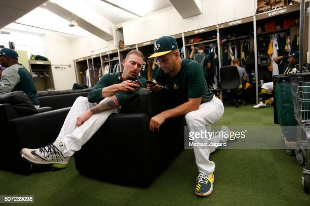 John Axford and Kendall Graveman of the Oakland Athletics relax in the clubhouse prior to the game against the Houston Astros at the Oakland Alameda...