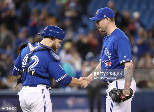 John Axford of the Toronto Blue Jays celebrates their victory with Russell Martin during MLB game action against the Kansas City Royals at Rogers...