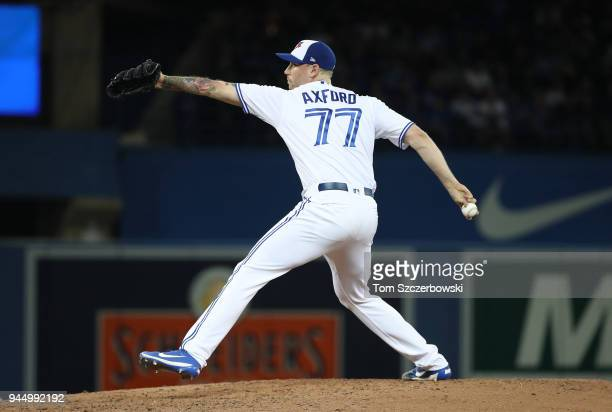 John Axford of the Toronto Blue Jays delivers a pitch in the fifth inning on Opening Day during MLB game action against the New York Yankees at...