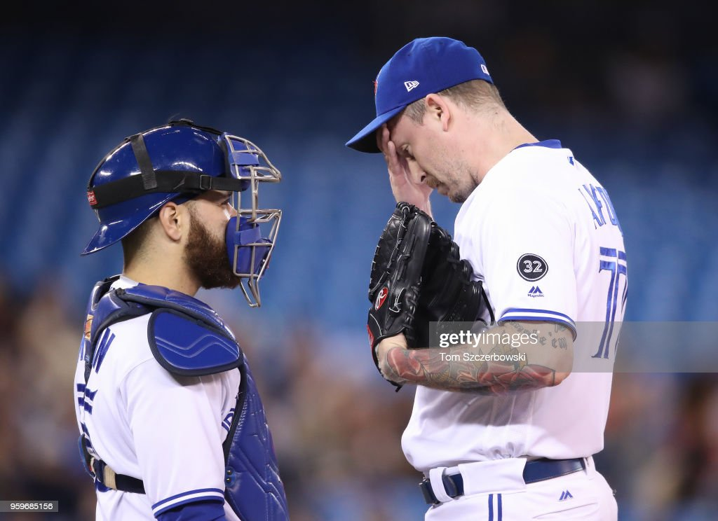 John Axford #77 of the Toronto Blue Jays is visited on the mound by Russell Martin #55 shortly after giving up a two-run home run in the sixth inning during MLB game action against the Oakland Athletics at Rogers Centre on May 17, 2018 in Toronto, Canada.