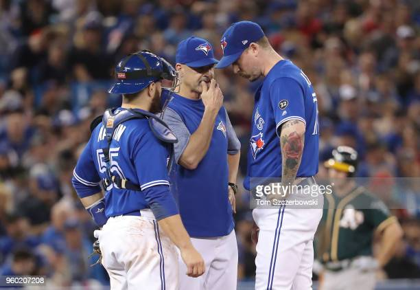 John Axford of the Toronto Blue Jays is visited on the mound by pitching coach Pete Walker in the eighth inning during MLB game action against the...