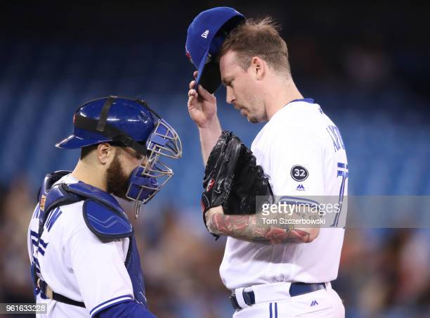 John Axford of the Toronto Blue Jays is visited on the mound by Russell Martin shortly after giving up a tworun home run in the sixth inning during...
