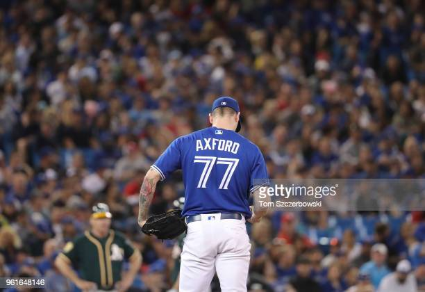 John Axford of the Toronto Blue Jays stands on the mound before delivering a pitch in the eighth inning during MLB game action against the Oakland...