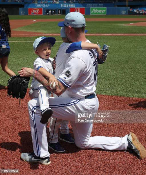 John Axford of the Toronto Blue Jays with his sons on Fathers Day shortly before the start of MLB game action against the Washington Nationals at...