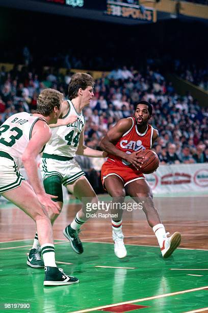 John Bagley of the Cleveland Cavaliers drives to the basket against Danny Ainge and Larry Bird of the Boston Celtics during a game played in 1985 at...